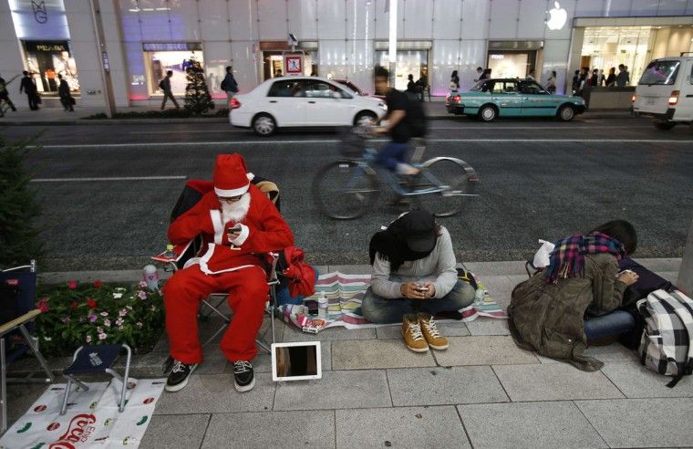A man dressed as Santa Claus sits along a street with other people as they wait for the release of Apple's new iPad mini in front of the Apple Store Ginza in Tokyo November 1, 2012. (Toru Hanai/Reuters)