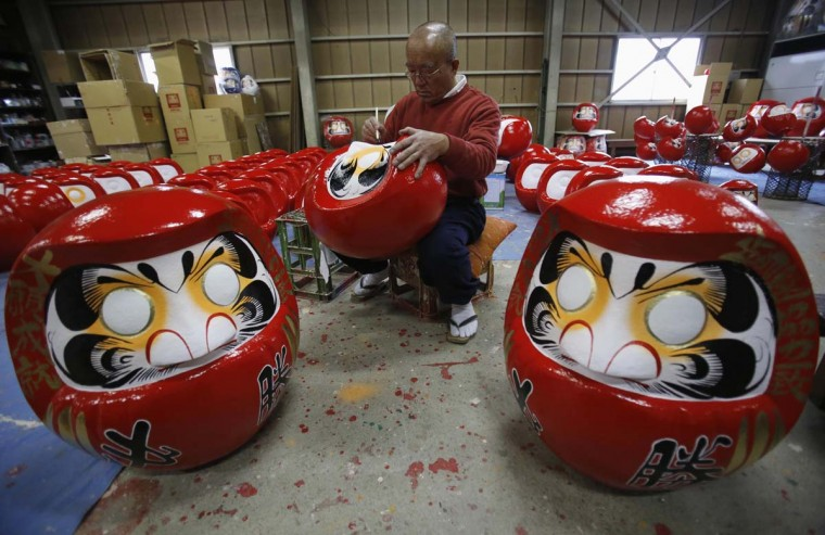 "Japanese craftsman Sumikazu Nakata adds the final touches on a Daruma doll, which is believed to bring good luck at his studio ""Daimonya"" in Takasaki, northwest of Tokyo. Daruma dolls, representing the Indian priest Bodhidharma, the founder of Zen Buddhism in China, is used to bring luck. It is also a favourite item of election candidates where they traditionally paint only one eye on the doll when they start their campaign and paint the other eye if they win in the election. The sales of Daruma has risen as candidates and campaign supporters purchased the lucky dolls ahead of the December 16 election, Nakata said. (Yuriko Nakao/Reuters photo)"