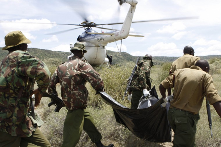 Kenyan police officers carry the slain body of their colleague killed by alleged Turkana cattle rustlers in a military-