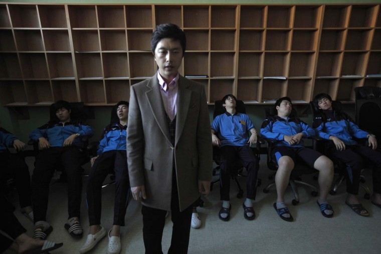 "A therapist hypnotizes students retaking college entrance exams, during a meditation session at Deung Yong Moon Boarding School in Kwangju. South Korea's exam hell is an annual event so full of pressure that many students are driven to despair, with some even taking their own lives. Some 140,000 of the test takers signed up for this year's entrance exam on November 8, 21 percent of the total, are high school graduates, according to government data. The really determined, or desperate, may decide to spend nine months at one of 40 private boarding schools like Deung Yong Moon (""Gateway to Success"") to dedicate their waking hours for the test. Picture taken October 30, 2012. (Kim Hong-Ji/Reuters)"