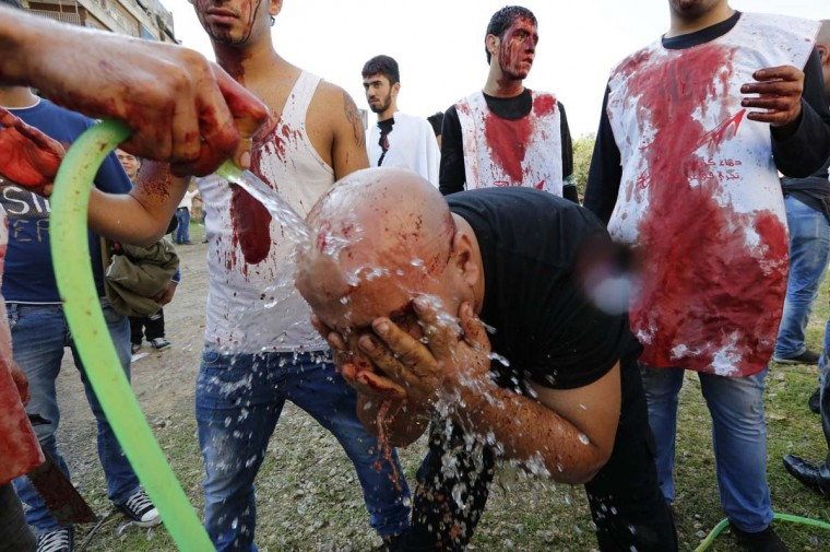A Lebanese supporter of the Shi'ite Amal movement washes his head from blood after tapping it with a razor at a Muharram procession to mark Ashura in Beirut November 25, 2012. (Jamal Saidi/Reuters)