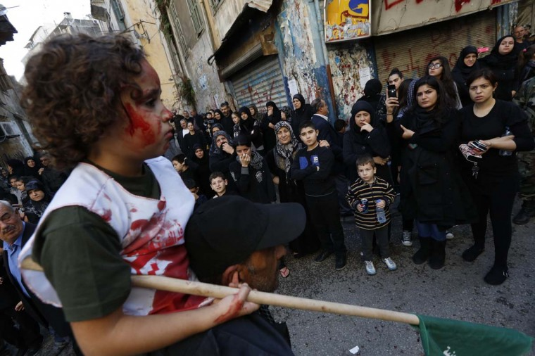 A Lebanese supporter of the Shi'ite Amal movement carries a girl with blood on her face as others watch at a Muharram procession to mark Ashura in Beirut November 25, 2012. (Jamal Saidi/Reuters)
