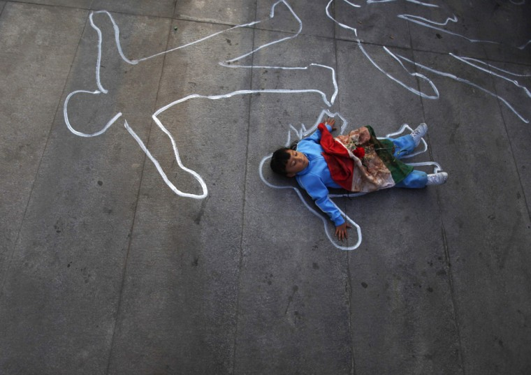 A boy with a Mexican flag, stained with paint to resemble blood, lies down in a chalk outline representing the body of a crime victim during a protest in Mexico City. People gathered at the Estela de Luz monument to protest against the government of Mexico's President Felipe Calderon who has been in power for six years. The turbulent presidency of Calderon comes to a close on December 1, six years after he ordered an offensive against drug cartels which led to a spike in violent crime and left at least 60,000 people dead and thousands more missing. (Edgard Garrido/Reuters)