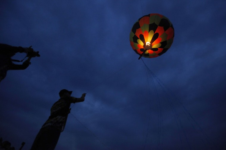 A man releases a paper balloon during a competition as part of the Day of the Dead celebrations in Milpa Alta November 1, 2012. (Edgard Garrido/Reuters)