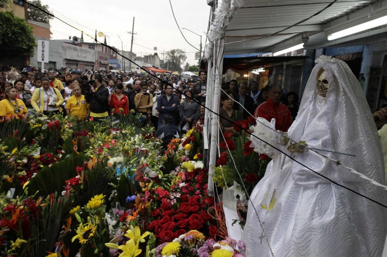 Followers of La Santa Muerte (The Saint of Death) attend a praying of the rosary during the main celebration at a market in Tepito, widely regarded as a dangerous neighbourhood in Mexico City, November 1, 2012. According to the organiser of the celebration, the cult to 'Saint Death' in Mexico has thousands of followers who offer her lit cigarettes, glasses of tequila, apples and flowers to express their gratitude for miracles and favours accredited to the saint. (Henry Romero/Reuters)