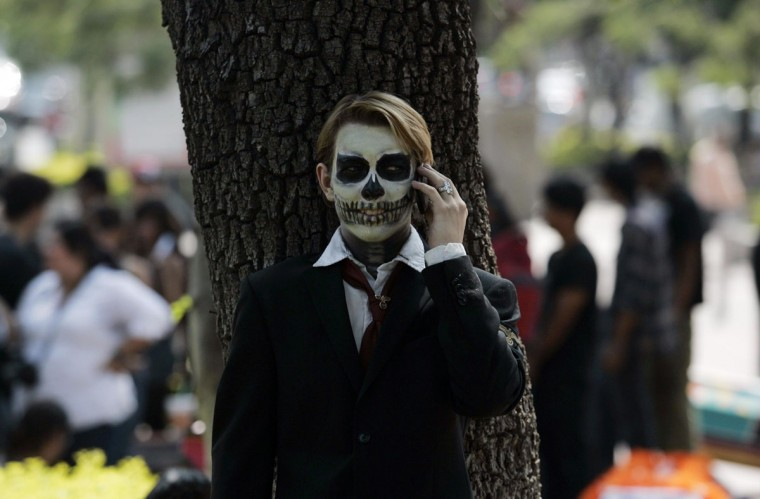 A fine arts student wears make-up as he talks on the phone during the Catrina's parade in Guadalajara October 26, 2012. (Alejandro Acosta/Reuters)