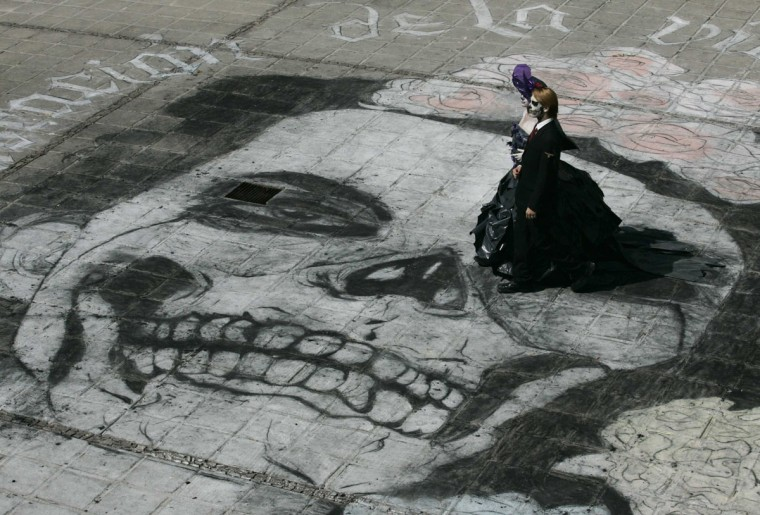 Fine arts students wearing make-up and costumes walk over a Catrina chalk drawing in Guadalajara October 26, 2012. (Alejandro Acosta/Reuters)