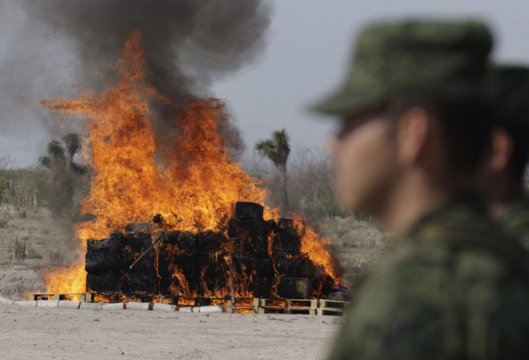 November 1, 2012: Soldiers stand at attention as a pile of marijuana and other drugs is being incinerated at the 7th Military Zone on the outskirts of Monterrey. (Daniel Beceriil/Reuters)