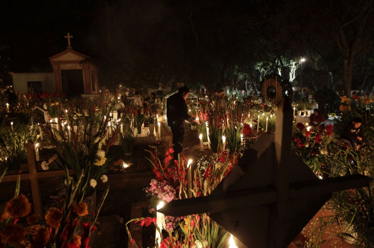 A man stands near the grave of a relative at a cemetery in Mexico City November 2, 2012. Mexicans celebrate the Day of the Dead to pay homage to their dead relatives, preparing meals and decorating the graves as an offering. (Henry Romero/Reuters)