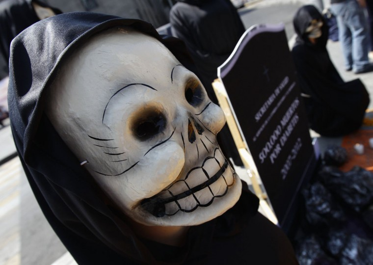 People in skull masks walk near an altar assembled in homage of people who died of diabetes and obesity in Mexico City, during a demonstration in front of the Mexican Ministry of Health in Mexico City October 31, 2012. The walk was part of the Day of the Dead, which is celebrated on November 1 in Mexico. (Henry Romero/Reuters)