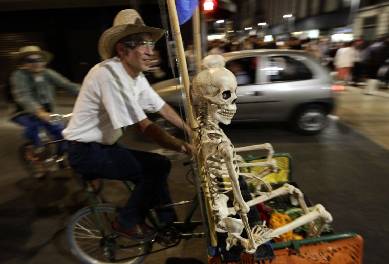 A man rides a tricycle carrying a replica human skeleton during a night cycling event in downtown Mexico City October 27, 2012. Several streets were closed to traffic as hundreds of people took part in the 'Night of the Dead' night cycling event organised by the city's authorities as part of celebrations for the Day of the Dead, according to local media. (Henry Romero/Reuters)
