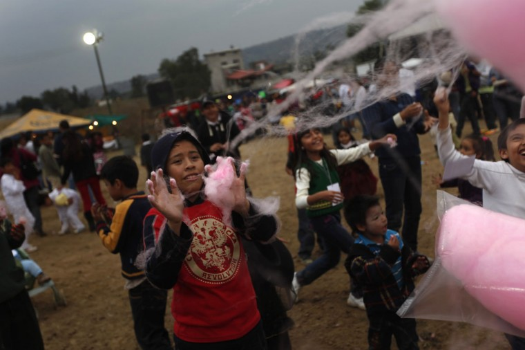 A boy catches cotton candy during a competition of paper balloon as part of the Day of the Dead celebrations in Milpa Alta November 1, 2012. (Edgard Garrido/Reuters)
