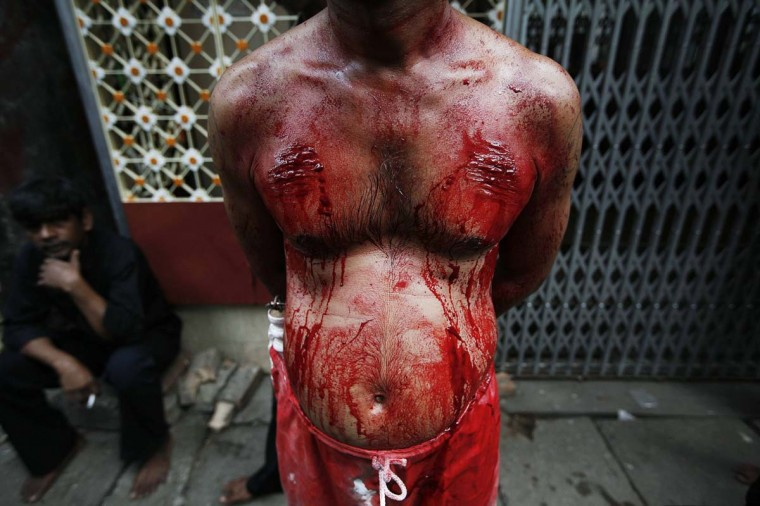 A Shi'ite Muslim man's body is seen bleeding as he rests after beating himself with iron chains during the Ashura religious festival in Yangon November 25, 2012. (Minzayar/Reuters)