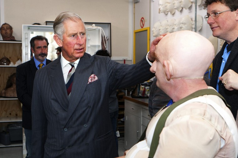 """Britain's Prince Charles (2nd L) meets actor Peter Hambleton (2nd R), who is dressed as Gloin the dwarf in The Hobbit movies, during a visit to the makeup department of film maker Peter Jackson's Weta Workshop in Wellington. The latest film """"The Hobbit: An Unexpected Journey"""" by Jackson, who also directed the Lord of the Rings trilogy, will premiere later this month in Wellington. (Jeff McEwan/Reuters)"""