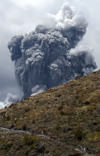 People make their way down a mountain path while a massive plume of ash billows up into the sky as Mount Tongariro erupts at Tongariro National Park, 300 km (186 miles) north of Wellington. New Zealand government geological agency GNS Science issued a warning on Wednesday after Mount Tongariro on the North Island erupted. The volcano previously erupted in August this year, the first time in more than a century. (Stefan Keller/Reuters)