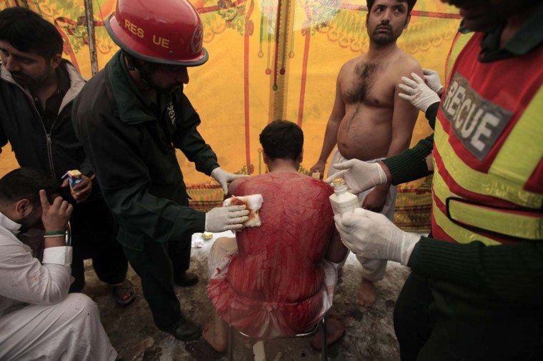 Paramedics treat a Pakistani Shi'ite Muslim man after he flagellated himself during an Ashura ceremony to mark the death of Hussein, the grandson of Prophet Mohammad in Rawalpindi November 25, 2012. (Faisal Mahmood/Reuters)