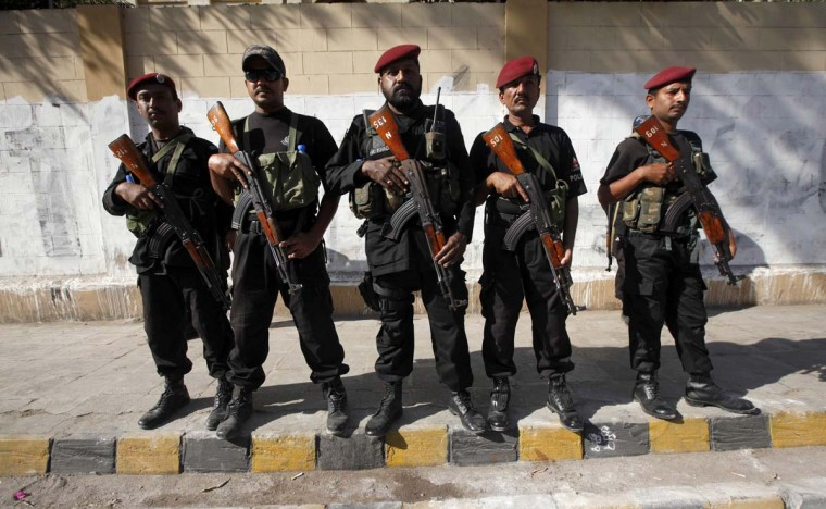 Pakistani security forces stand guard during an Ashura ceremony to mark the death of Hussein, the grandson of Prophet Mohammad in Karachi November 25, 2012. (Athar Hussain/Reuters)