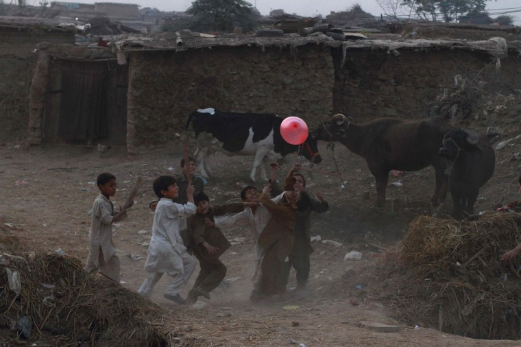 Boys play with a balloon at a slum on the outskirts of Islamabad. (Faisal Mahmood/Reuters)