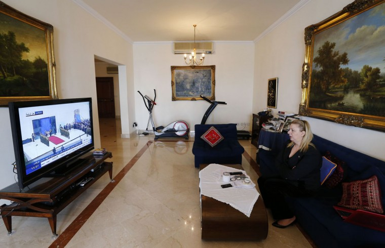 Suha Arafat, widow of the late Palestinian leader Yasser Arafat, watches the wreath laying ceremony after her husband's exhumation in the West Bank city of Ramallah, on television from her apartment in Sliema, outside Valletta. Forensic experts took samples from Yasser Arafat's buried corpse in the West Bank on Tuesday, trying to determine if he was murdered by Israeli agents using the hard-to-trace radioactive poison, Polonium. (Darrin Zammit Lupi/Reuters)