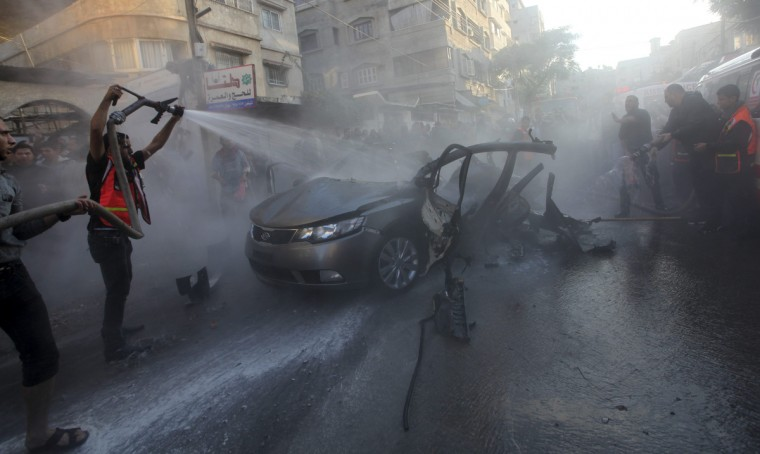 Palestinians help extinguish the fire after an Israeli air strike on the car of Hamas's top commander in Gaza City. An Israeli official said on Wednesday the assassination of Hamas's top commander in the Gaza Strip was not the end of Israel's assault on the coastal territory and more strikes would follow. Ahmed Al-Jaabari, Hamas's military chief, was killed when his car was hit by an Israeli airstrike. Multiple other Israeli attacks rocked the Gaza Strip. (Reuters)