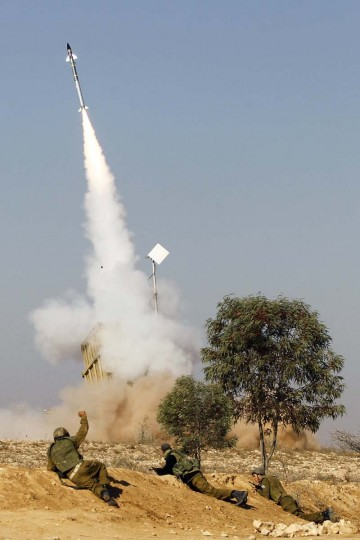 Israeli soldiers watch as an Iron Dome launcher fires an interceptor rocket near the southern city of Beersheba. Hamas fired dozens of rockets into southern Israel on Thursday, killing three people, and Israel launched numerous air strikes across the Gaza Strip, threatening a wider offensive to halt repeated Palestinian salvoes. (Baz Ratner/Reuters photo)