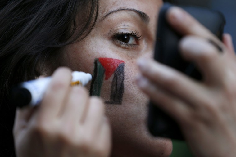 NOVEMBER 20: A member of the Palestinian community in Chile paints a Palestinian flag on her face during a protest against Israel's military operations in Gaza, at downtown Santiago. (Ivan Alvarado/Reuters)