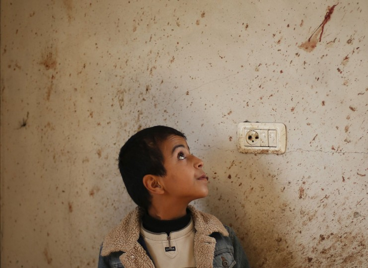 The brother of Palestinian boy Faris Basyoni, who was killed in an Israeli air strike, looks at his blood on a wall at his family's damaged house in Beit Hanoun in the northern Gaza Strip. Basyoni was killed on Thursday night when an Israeli air strike hit his family house. Egypt opened a tiny window to emergency peace diplomacy in Gaza on Friday, but hopes for even a brief ceasefire while its prime minister was inside the bombarded enclave to talk to leaders of the Islamist Hamas movement were immediately dashed. (Suhaib Salem/Reuters)