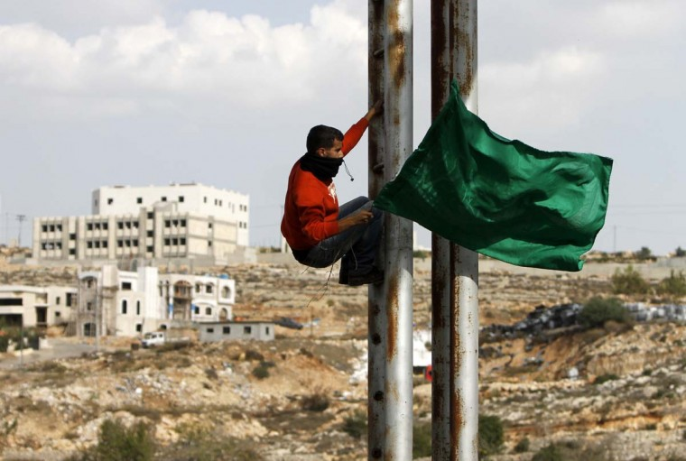 NOVEMBER 18 — A man with a Palestinian flag climbs a street pole during clashes with Israeli security forces outside Ofer prison near the West Bank city of Ramallah November 18, 2012. The clashes broke out following a protest against Israel's military operation in the Gaza Strip. (Mohamad Torokman/Reuters)