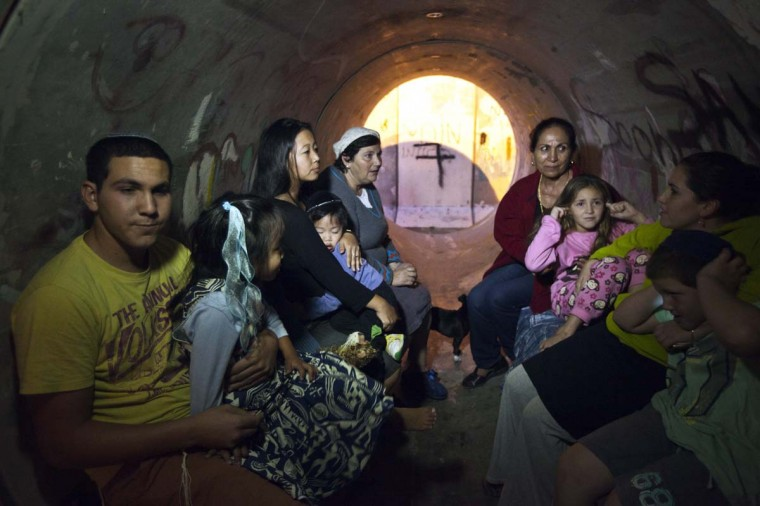 NOVEMBER 15 — Israelis sit inside a sewage pipe used as shelter during alert, warning of incoming rockets, in the southern community of Nitzan, near Ashdod November 15, 2012. (Nir Elias/Reuters)
