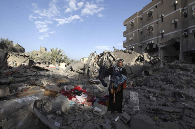 NOVEMBER 18 — A Palestinian woman holds her belongings at the site of her destroyed house after an Israeli air strike in Rafah in southern Gaza Strip November 18, 2012. (Ibrahemm Abu Mustafa/Reuters)