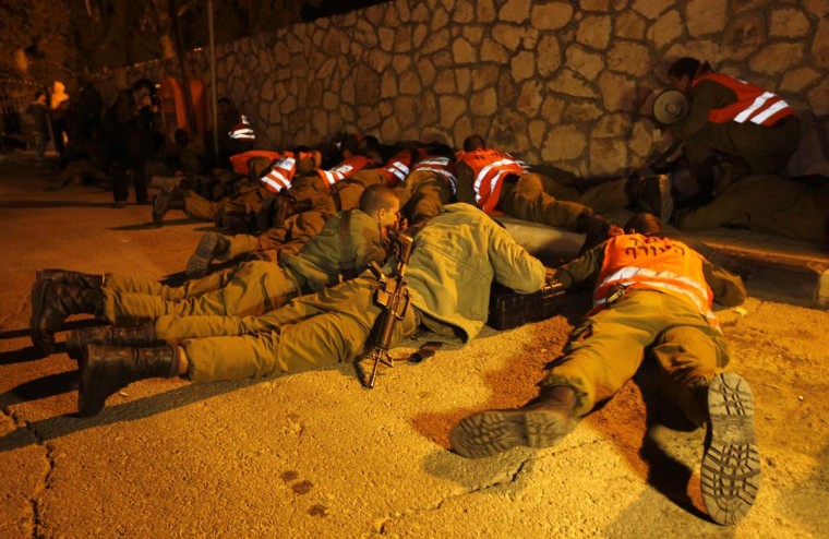 NOVEMBER 15 — Israeli soldiers take cover as an air raid siren warns of incoming rockets before the funeral of Aaron Smadja, one of the three Israelis killed by a rocket fired from Gaza, at a cemetery in the southern city of Kiryat Malachi November 15, 2012. (Ronen Zvulun/Reuters)