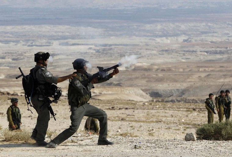 NOVEMBER 14 — An Israeli border police officer fires tear gas towards Palestinian activists attempting to block a road in the West Bank town of Jericho November 14, 2012. (Ammar Awad/Reuters)
