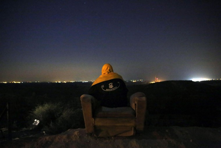NOVEMBER 20: A private Israeli security guard sits on an armchair as he watches the fighting from a hill outside the northern Gaza Strip. A Hamas official said on Tuesday Egypt had brokered a Gaza ceasefire deal that would go into effect within hours, but a spokesman for Israeli Prime Minister Benjamin Netanyahu said 'we're not there yet.' (Yannis Behrakis/Reuters)
