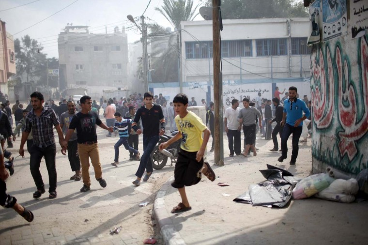 NOVEMBER 18 — Palestinians run after an Israeli air strike on a house in Gaza City November 18, 2012. Israel bombed militant targets in Gaza for a fifth straight day on Sunday. (Ahmed Jadallah/Reuters)