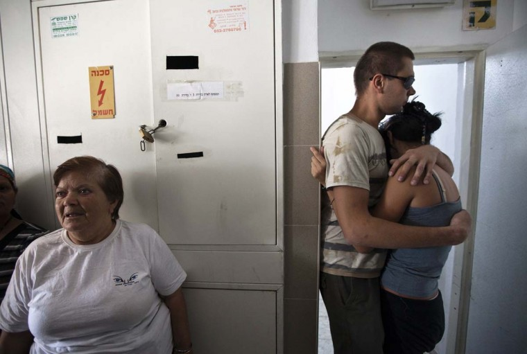 NOVEMBER 18 — Israelis embrace as they take cover in a stairwell during the sounding of a siren warning of incoming rockets in the coastal city of Ashkelon November 18, 2012. (Nir Elias/Reuters)