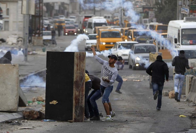 NOVEMBER 17 — Palestinian protesters throw stones during clashes with Israeli security forces against Israel's military operation in the Gaza Strip, in Qalandiya checkpoint near the West Bank city of Ramallah November 17, 2012. (Ammar Awad/Reuters)