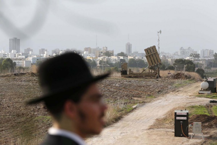 NOVEMBER 17 — An ultra-Orthodox Jewish man stands in front of an Iron Dome rocket shield battery in the southern city of Ashdod November 17, 2012. Israeli aircraft bombed Hamas government buildings in Gaza on Saturday, including the prime minister's office, after Israel's cabinet authorised the mobilisation of up to 75,000 reservists, preparing for a possible ground invasion. (Darren Whiteside/Reuters)