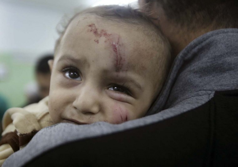NOVEMBER 17 — A wounded Palestinian child is carried into a hospital after an Israeli air strike in the northern Gaza Strip November 17, 2012. (Ali Hassan/Reuters)