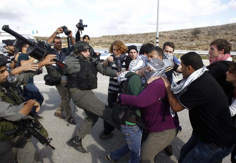 NOVEMBER 14 — Israeli border police scuffle with Palestinian and international activists as they block a road used by Israeli settlers near the West Bank village of Shuqba, northwest of Ramallah November 14, 2012. (Mohamad Torokman/Reuters)