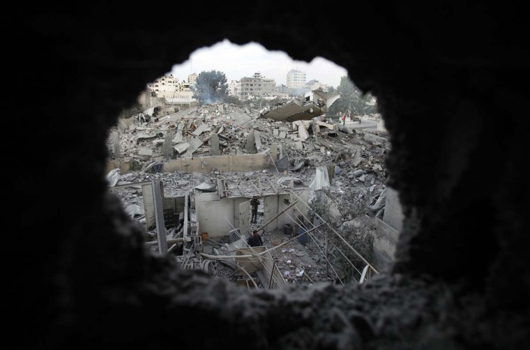 NOVEMBER 17 — Palestinians are seen through a hole in the wreckage as they inspect the destroyed office building of Hamas Prime Minister Ismail Haniyeh in Gaza City November 17, 2012. (Suhaib Salem/Reuters)