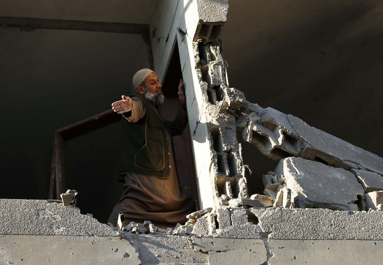 NOVEMBER 15 — A Palestinian man checks his damaged house after Israeli air strikes in Gaza City November 15, 2012. Israel exchanged the fiercest fire with Hamas in years after assassinating its military mastermind and threatening a wider offensive in the Gaza Strip to stem Palestinian rocket salvoes. (Suhaib Salem/Reuters)