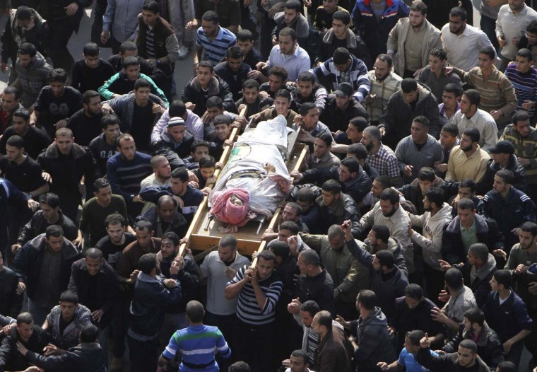 Palestinians carry the body of Ahmed Al-Jaabari, Hamas's military mastermind, during his funeral in Gaza Cityd. A Hamas rocket killed three Israelis north of the Gaza Strip on Thursday, drawing the first blood from Israel as the Palestinian death toll rose to 13 and a military showdown lurched closer to all-out war with an invasion of the enclave. The offensive began on Wednesday when a precision Israeli air strike assassinated Ahmed Al-Jaabari, and Israel shelled the enclave from land, air and sea. (Ali Hassan/Reuters photo)