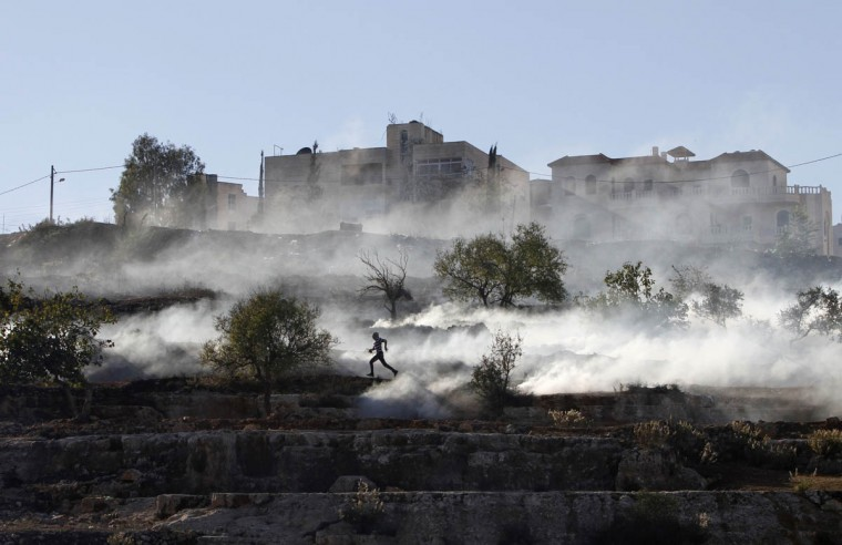 A Palestinian stone-thrower runs after Israeli security forces fired tear gas during clashes against Israel's military operation in Gaza, outside Ofer prison near the West Bank city of Ramallah. A rocket fired from the Gaza Strip landed close to Tel Aviv on Thursday, in the first attack on Israel's biggest city in 20 years, raising the stakes in a military showdown between Israel and the Palestinians that is moving towards all-out war. (Mohamad Torokman/Reuters)