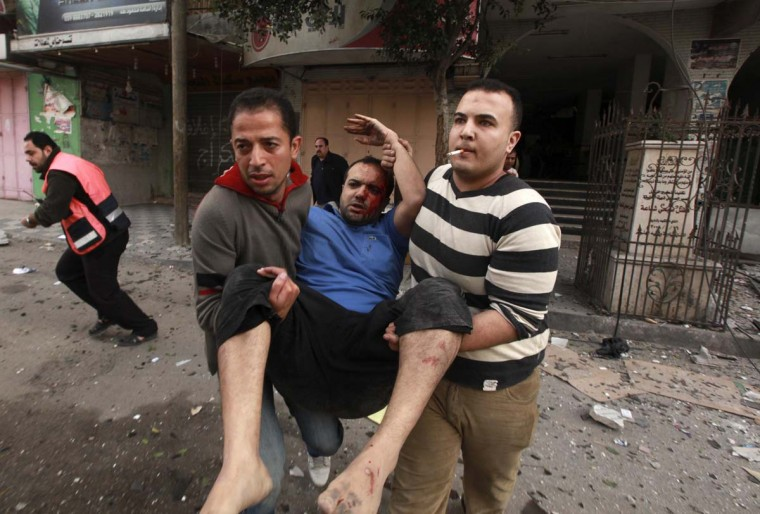 Palestinians evacuate a wounded man after an Israeli air strike, witnessed by a Reuters journalist, on a floor in a building that also houses media offices in Gaza City November 19, 2012. Egypt's prime minister said on Monday that an agreement brokered by Cairo to stop the fighting between Israel and the Palestinians in Gaza could be close. (Mohammed Salem/Reuters)