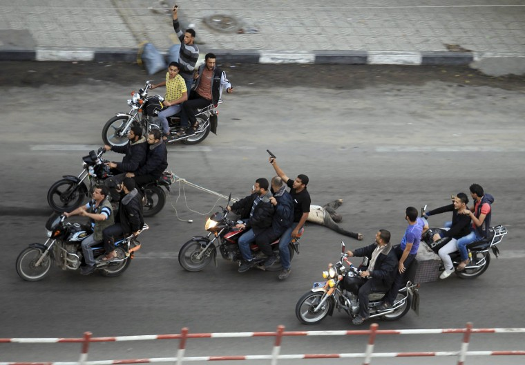 NOVEMBER 20: Palestinian gunmen ride motorcycles as they drag the body of a man, who was suspected of working for Israel, in Gaza City. (Mohammed Salem/Reuters)