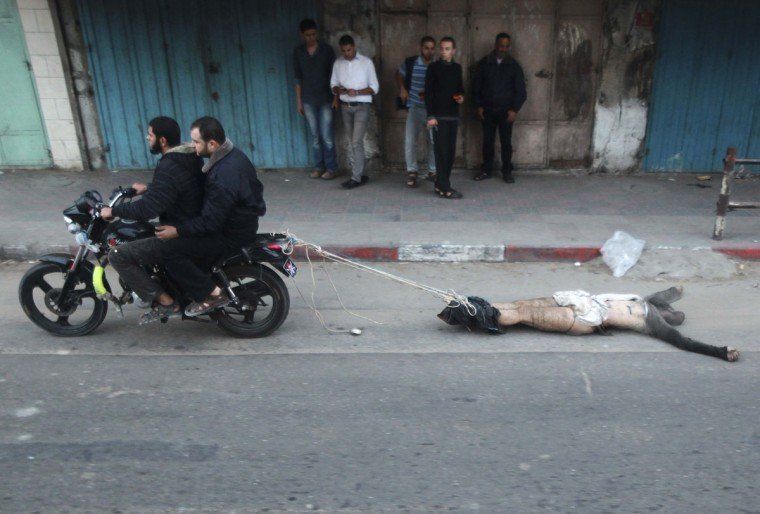 NOVEMBER 20: Palestinian gunmen ride a motorcycle as they drag the body of a man, who was suspected of working for Israel, in Gaza City. Palestinian gunmen shot dead six alleged collaborators in the Gaza Strip who 'were caught red-handed,' according to a security source quoted by the Hamas Aqsa radio on Tuesday. (Mohammed Salem/Reuters)