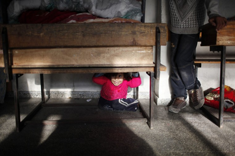 NOVEMBER 20: A displaced Palestinian girl, who fled her family's house, sits under a bench in a classroom as she stays with her family at a United Nations-run school in Gaza City. From the sandy expanses of the northern Gaza Strip, Palestinian families are fleeing their homes destroyed by airstrikes, but refuse to blame the Hamas rocket crews who draw Israeli fire. (Ahmed Jadallah/Reuters)