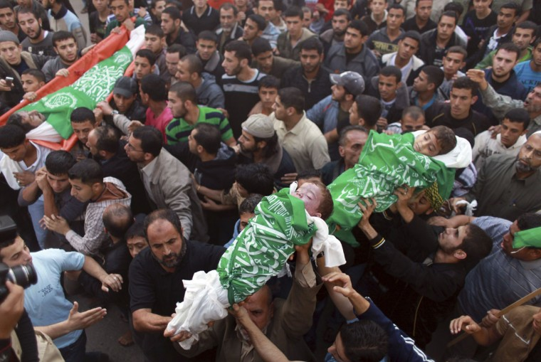 NOVEMBER 20: Palestinians carry the bodies of two children, Suhaib (C) and Mohammed, and their father Fuad Hejazi during their funeral in Beit Lahiya in the northern Gaza Strip. The two children and their father were killed when an Israeli air strike in the Gaza town of Beit Lahiya crushed their home on Monday, the Hamas Health Ministry said. (Mohammed Salem/Reuters)