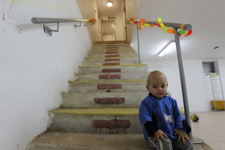 An Israeli boy sits on the stairs in a bomb shelter in the southern city of Ashkelon. Israeli tanks and troops massed outside Gaza and the military said on Friday it was calling up 16,000 reservists, signs of a possible imminent invasion of the Palestinian enclave after 48 hours of air strikes. (Amir Cohen/Reuters)