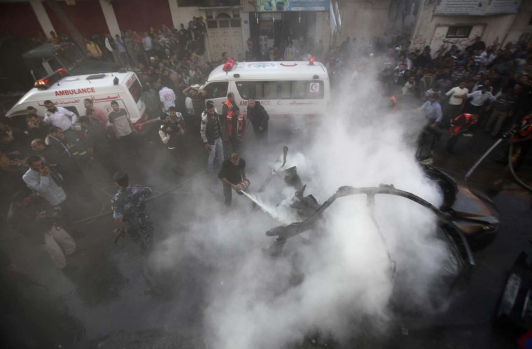 NOVEMBER 14 — Palestinians extinguish the fire after an Israeli air strike on a car in Gaza City November 14, 2012. (Ali Hassan/Reuters)